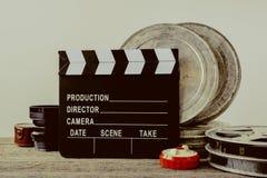 Clapperboard, cajas de la lata con la película y la lente Fotos de archivo libres de regalías