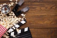 Clapperboard, carretel de filme e pipoca no fundo de madeira, vista superior Imagem de Stock Royalty Free