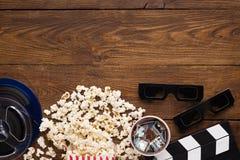 Clapperboard, carretel de filme e pipoca no fundo de madeira, vista superior Foto de Stock Royalty Free