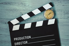 Clapperboard and clock. Clapperboard and old round clock lie on the painted board Stock Photography