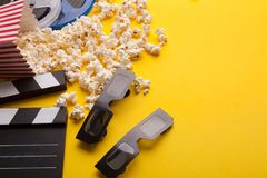 Clapperboard, 3D glazen en popcorn op gele achtergrond Stock Afbeelding