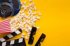 Clapperboard, 3D glazen en popcorn op gele achtergrond Stock Afbeeldingen