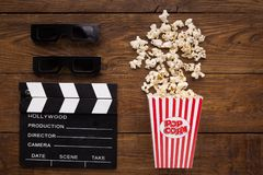 Clapperboard, 3D glazen en popcorn op houten achtergrond Stock Afbeeldingen