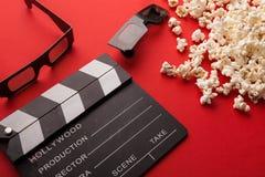 Clapperboard, 3D glazen en popcorn op rode achtergrond Stock Foto