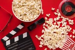Clapperboard, 3D glazen en popcorn op rode achtergrond Royalty-vrije Stock Afbeeldingen