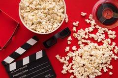 Clapperboard, 3D glazen en popcorn op rode achtergrond Royalty-vrije Stock Afbeelding