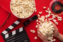 Clapperboard, 3D glazen en popcorn op rode achtergrond Royalty-vrije Stock Fotografie