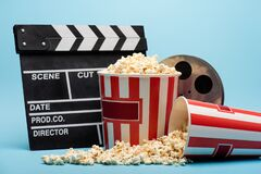 clapperboard, film reel and buckets with popcorn on blue, cinema concept.