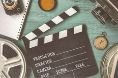 Clapperboard and a film reel. A stop watch, a notebook and a lens on the table Royalty Free Stock Photo