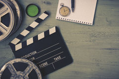 Clapperboard and a film reel. A stop watch, a notebook and a lens on the table Royalty Free Stock Photos