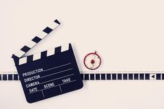 Clapperboard, film and timer. Clapperboard, a piece of film and a red timer lie on a light background Stock Photos