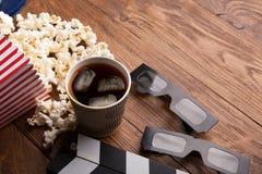 Clapperboard, Filmrolle und Popcorn auf hölzernem Hintergrund stockbild