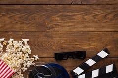 Clapperboard, filmspoel en popcorn op houten achtergrond, hoogste mening Stock Foto's