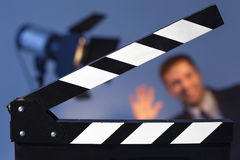 Clapperboard and flashlight with TV presenter in a suit or model. Man waving at the camera Stock Photography