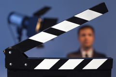 Clapperboard and flashlight with TV presenter in a suit or model. Man waving at the camera Stock Image