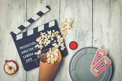 Clapperboard, movie reel and popcorn. Clapperboard,, coil with film, popcorn, red filter, timer and two tickets for the film was shot from above Royalty Free Stock Photos
