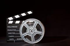 Clapperboard och filmrulle på den svarta bakgrunden royaltyfri foto