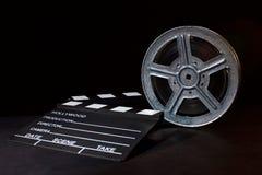 Clapperboard och filmrulle på svart fotografering för bildbyråer