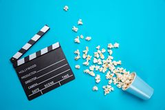 Clapperboard and pop corn on blue color background, top view. Cinema film concept. Fresh salty pop corn spilled out of a carton container and movie clapper board stock photography