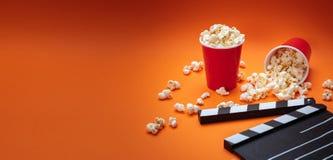 Clapperboard and pop corn on orange color background stock image