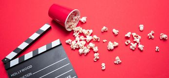 Clapperboard and pop corn on red color background royalty free stock photography