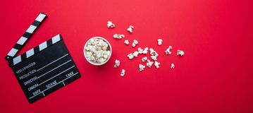 Clapperboard and pop corn on red color background, copy space royalty free stock photography