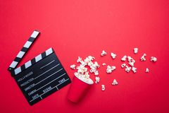 Clapperboard and pop corn on red color background, top view royalty free stock images