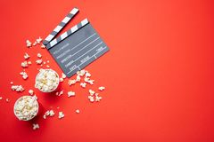 Clapperboard and pop corn on red color background, top view. Cinema for two concept. Fresh salty pop corn and movie clapper board, red color background, top view royalty free stock image