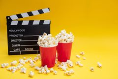 Clapperboard and pop corn on yellow color background stock images