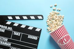 Clapperboard and popcorn. On color background Royalty Free Stock Photos