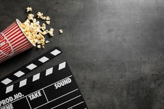 Clapperboard and popcorn. On table Royalty Free Stock Photography