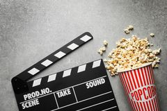 Clapperboard and popcorn. On table Stock Photography
