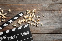Clapperboard and popcorn. On wooden background Stock Photos