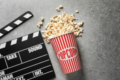 Clapperboard and popcorn. On table Stock Images