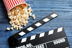 Clapperboard and popcorn. On wooden background Royalty Free Stock Photo