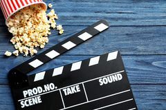 Clapperboard and popcorn. On wooden background Royalty Free Stock Image