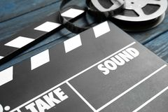 Clapperboard and reel on wooden table, closeup. Cinema production stock photo