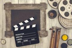 Clapperboard, spoelen van film en een driepoot Stock Foto