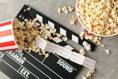 Clapperboard, tickets and buckets with popcorn on grey background