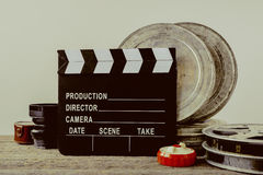 Clapperboard, tin boxes with film and lens Royalty Free Stock Photos