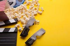 Clapperboard, vidros 3D e pipoca no fundo amarelo Imagem de Stock