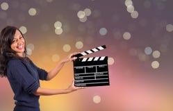 Clapperboard-Zeichengriff durch weibliche Hände stockfotografie