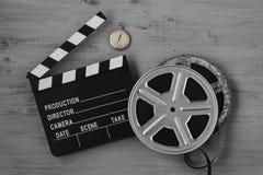 Clapperboards, zwei Filmrollen und alte Uhr Stockbild