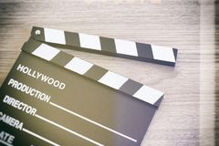 Clapperbräde, filmclapper på träbackgrond arkivfoto
