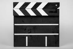Clapperen för att indikera början av en film eller ett videogem gjorde av trä och målade svartvitt med band i det stängt arkivfoto
