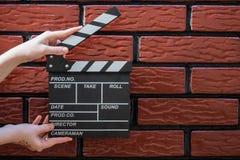 Clapperplattor, händer för kvinna` s och en filmclapper med en tegelsten b fotografering för bildbyråer