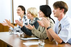Clapping. Successful applauding young people sitting at the table in the office Royalty Free Stock Photo