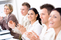 Clapping business people. Five business people sitting in a row, smiling and clapping on business training. Selective focus placed on businesswoman in middle stock photo