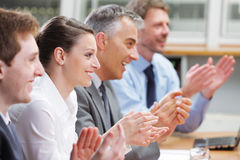 Clapping business people. Group of cheerful businesspeople sitting in a row on a presentation and clapping Stock Images