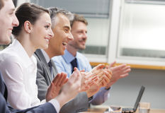 Clapping business people. Group of cheerful businesspeople sitting in a row on a presentation and clapping Royalty Free Stock Photos